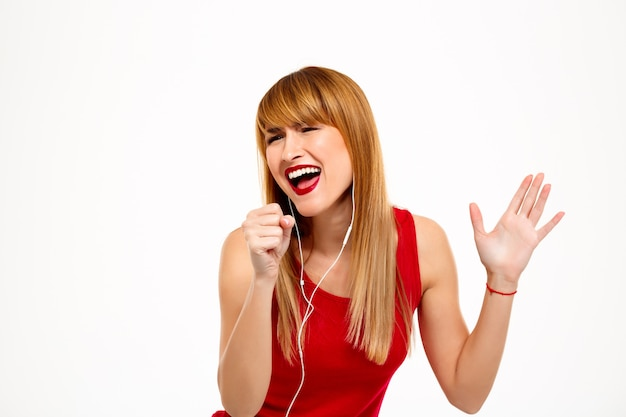 Belle jeune femme écoutant de la musique dans les écouteurs sur mur blanc