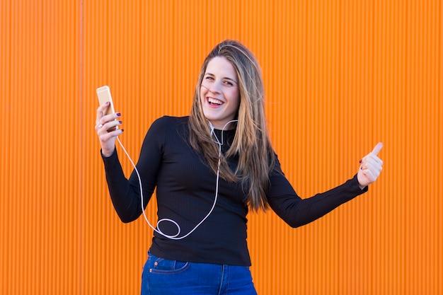 Belle jeune femme écoutant de la musique avec des écouteurs et s'amuser sur le mur orange