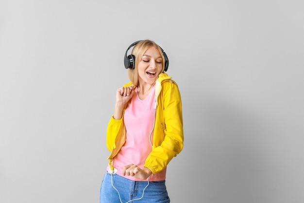 Belle jeune femme écoutant de la musique sur la lumière