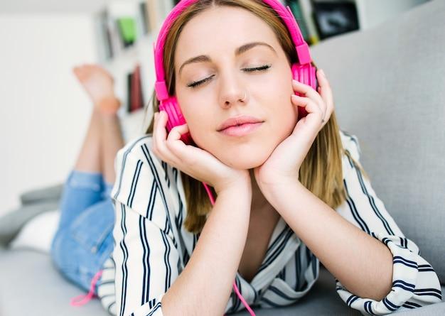 Belle jeune femme écoutant de la musique à la maison.