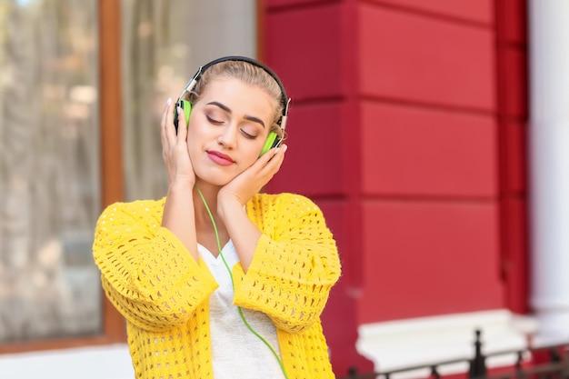 Belle jeune femme écoutant de la musique en plein air