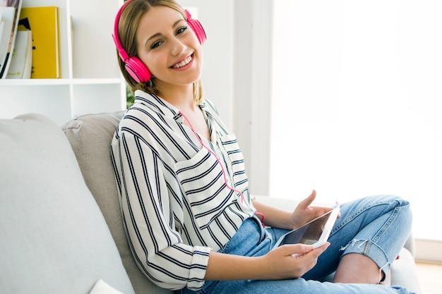 Belle jeune femme écoutant de la musique avec une tablette numérique.