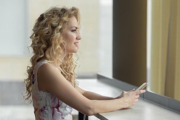 Belle jeune femme écoute de la musique par son smartphone au café.