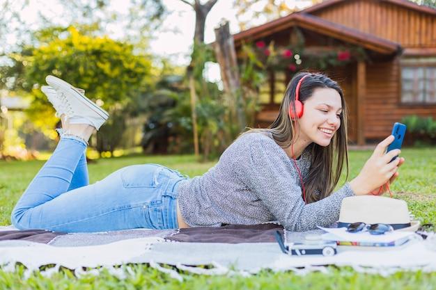 Belle jeune femme avec des écouteurs profitant de la musique à l'extérieur - belle jeune femme heureuse avec des écouteurs écoutant de la musique allongée sur l'herbe.