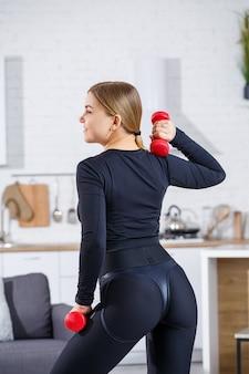 Belle jeune femme élancée fait du sport à la maison dans un haut et des leggings. fitness à la maison pour un beau corps. exercices avec haltères pour le corps féminin. mode de vie sain.