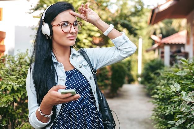 Belle jeune femme élégante à l'aide de smartphone, casque, lunettes, été, tenue en denim vintage, souriant, heureux, positif
