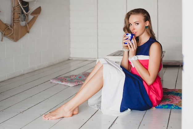 Belle jeune femme élégante au café de la mer, boire un cappuccino chaud, style resort, tenue à la mode, souriant, robe de couleurs marines, assis sur le sol, ancre et bouée de sauvetage sur fond, vacances, se détendre