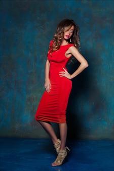 Belle jeune femme élégante aux cheveux châtain clair, à la mode maquillage et coiffure, posant dans une robe moulante rouge et des talons dorés