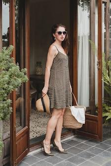 Belle jeune femme élégante dans un hôtel de villégiature, vêtue d'une robe à la mode, style safari, chapeau de paille, vacances d'été, tenue bohème, sac de plage, lunettes de soleil