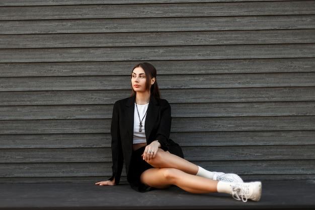 Belle jeune femme élégante dans un manteau noir avec des baskets à la mode blanches