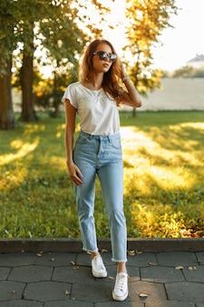 Belle jeune femme élégante dans les vêtements de marque de mode debout dans le parc au coucher du soleil