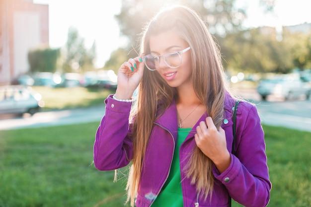 Belle jeune femme élégante en lunettes de soleil marchant dans le parc par une journée d'été ensoleillée.