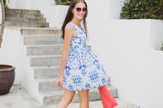 Belle jeune femme élégante en robe imprimée bleue, sac rouge, lunettes de soleil, bonne humeur, tenue à la mode, vêtements à la mode, souriant, été, accessoires