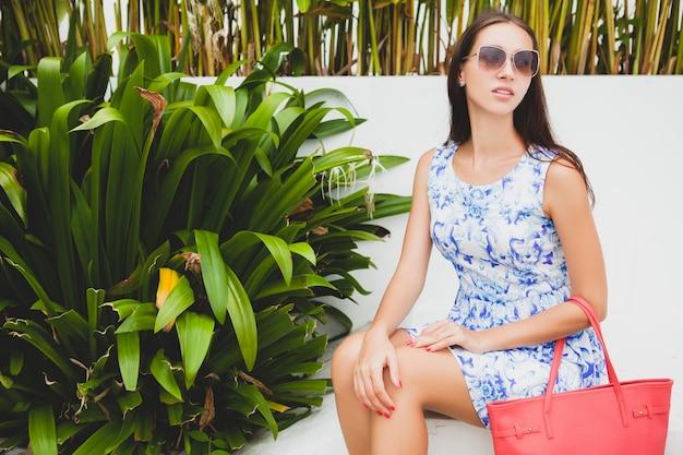Belle jeune femme élégante en robe imprimée bleue, sac rouge, lunettes de soleil, tenue à la mode, vêtements à la mode, souriant, assis, été, accessoires