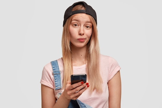 Belle jeune femme élégante tient un téléphone intelligent moderne