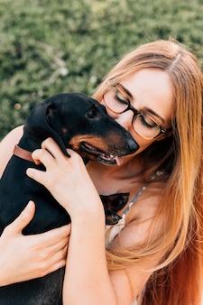 Belle jeune femme embrasse son chien