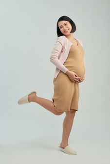 Belle jeune femme émotionnelle enceinte posant isolé sur fond blanc.