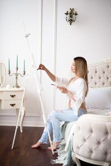 Belle jeune femme enceinte artiste peinture à la maison pivoines roses