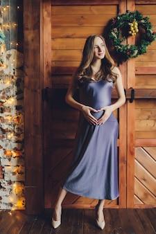 Belle jeune femme enceinte aux cheveux blonds et maquillage doux en robe rouge à la mode posant près du studio