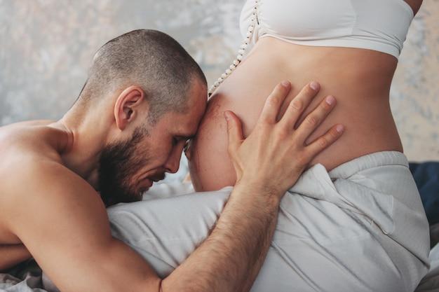 La belle jeune femme enceinte aux longs cheveux bouclés en vêtements ethniques et perles de mala avec son mari.