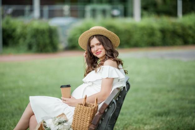 Belle jeune femme enceinte boit du cappuccino dans le parc