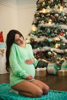 Belle jeune femme enceinte décore un arbre de noël