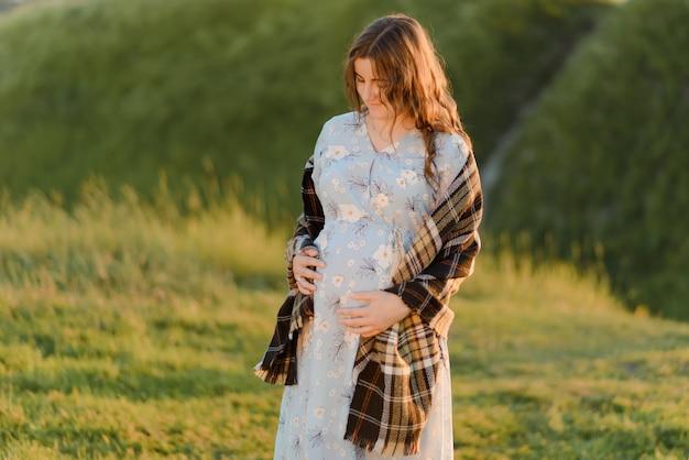 Belle jeune femme enceinte mettant ses mains sur son ventre et le regardant avec amour. nouveau née.