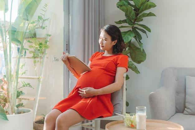Belle jeune femme enceinte robe rouge asiatique lisant un livre debout devant la fenêtre
