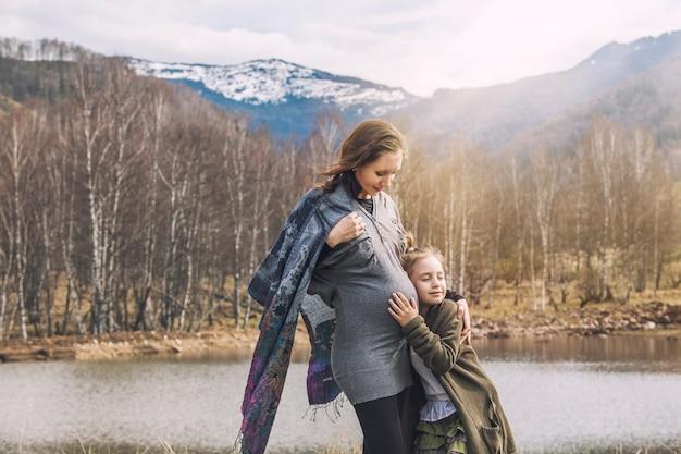 Belle jeune femme enceinte et sa petite fille souriante