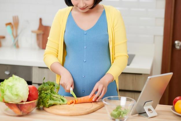 Belle jeune femme enceinte souriante, préparer des aliments sains avec beaucoup de fruits et légumes à la cuisine à domicile