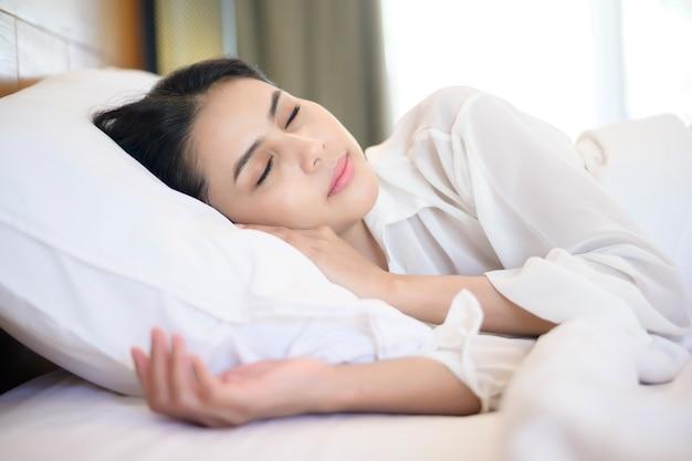Belle jeune femme endormie dans son lit à la maison