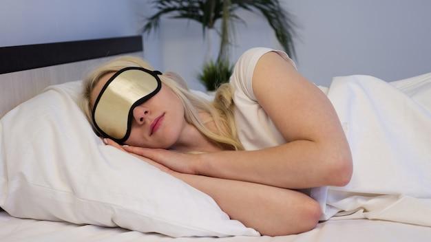 Belle jeune femme endormie dans son lit avec masque pour les yeux