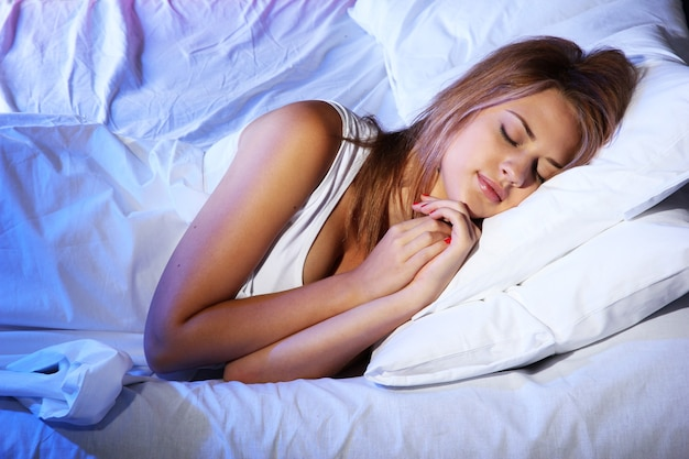 Belle jeune femme endormie sur le lit dans la chambre