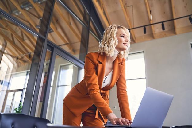 Belle jeune femme entrepreneure souriante et joyeuse avec sa main sur un clavier d'ordinateur portable avec impatience