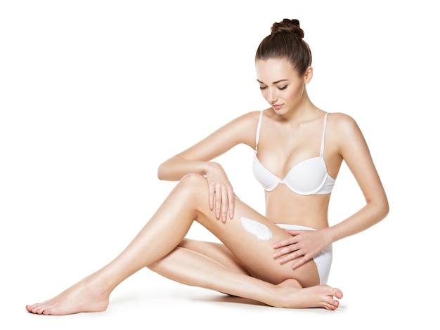 Belle jeune femme épilant ses jambes par épilation à la cire - studio sur fond blanc