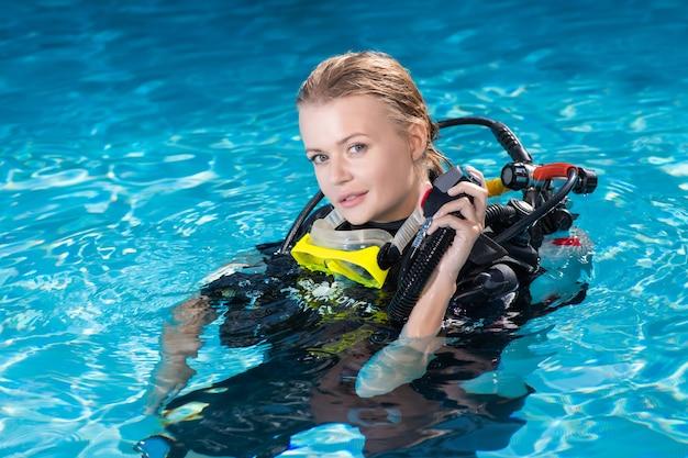 Belle jeune femme en équipement de plongée et plongée