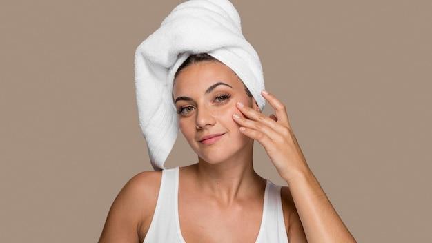 Belle jeune femme essayant des produits cosmétiques