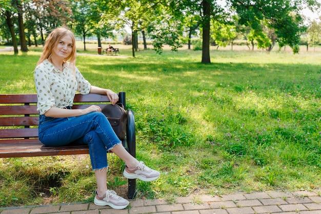La belle jeune femme est assise sur un banc. femme élégante reste dans le parc.