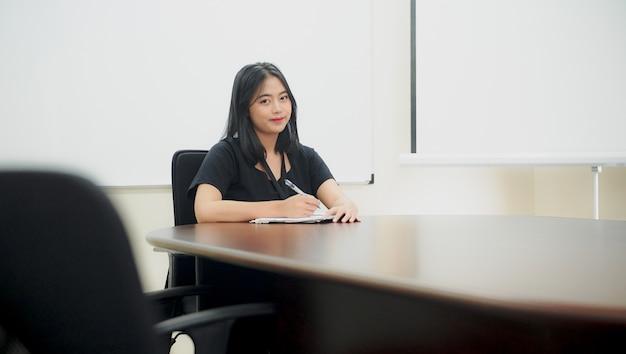 Belle jeune femme est assise sur une chaise et prête à écrire des activités événementielles au bureau