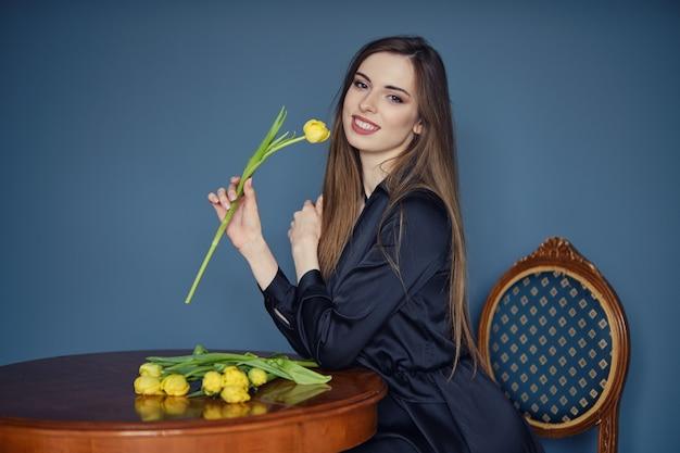 Belle jeune femme est assise derrière la table dans un style victorien avec des tulipes jaunes à la main