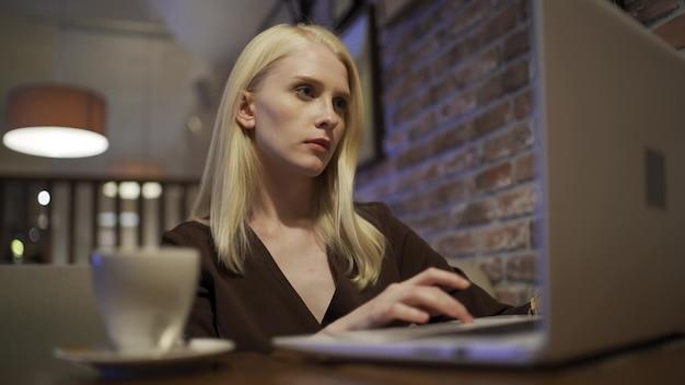 Une belle jeune femme est assise sur internet via un ordinateur portable et feuillette le fil d'actualité dans un restaurant. repos dans la grande ville, week-end. gros plan, 4k uhd.