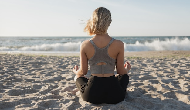 Belle jeune femme est assise sur la plage