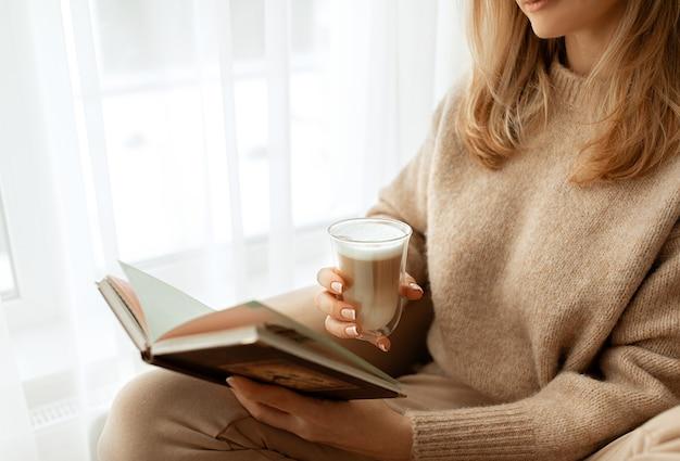 Belle jeune femme est assise près de la fenêtre en pull tricoté beige détient le bloc-notes et le verre cappuccino de café avec de la mousse blanche