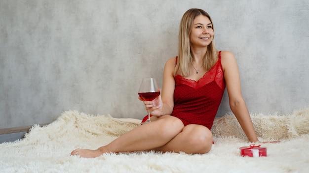 Une belle jeune femme est assise en sous-vêtements rouges sur un plaid blanc avec du vin à la main. matin de la saint-valentin