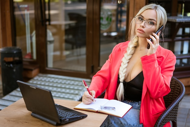 Une belle jeune femme est assise à une table avec un ordinateur portable dans la rue dans un café écrit dans un cahier