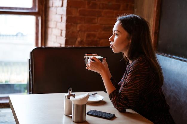 Une belle jeune femme est assise à une table avec une tasse de café près de la fenêtre d'un café, regardant sur le côté avec un regard pensif