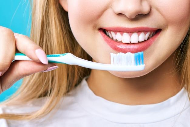 Belle jeune femme est engagée dans le nettoyage des dents