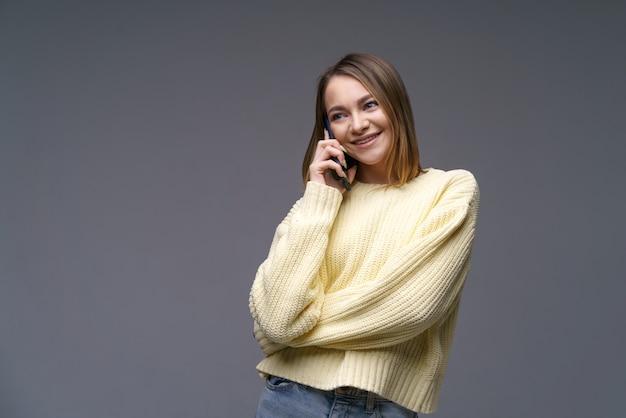 Belle jeune femme d'ethnie caucasienne parlant au téléphone dans un pull volumétrique jaune sur une surface grise aux yeux bleus