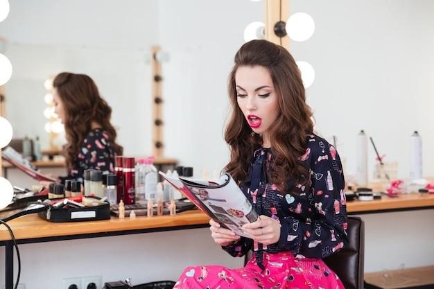 Belle jeune femme étonnée assise dans un salon de beauté et lisant un magazine de mode