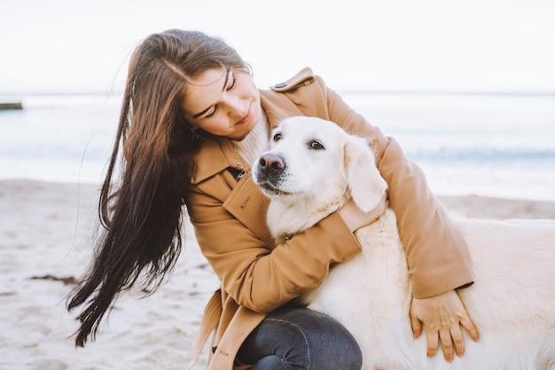 Belle jeune femme étreignant avec son chien golden retreiver
